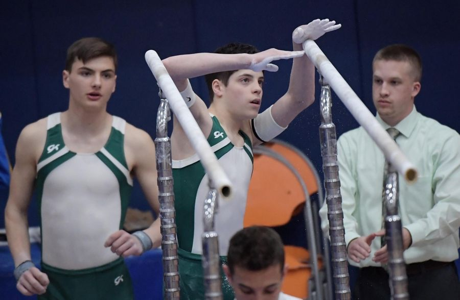 Glenbard West's Shea Rudolph measures the parallel bars with teammate Alexander Demeris at the boys gymnastics state finals at Hoffman Estate High School Saturday night.