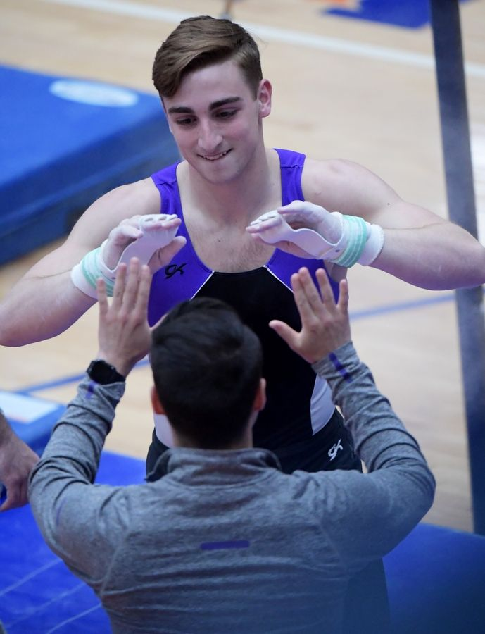 Downers Grove North's Lukas Elisha celebrates his high bar performance at the boys gymnastics state finals at Hoffman Estate High School Saturday night.