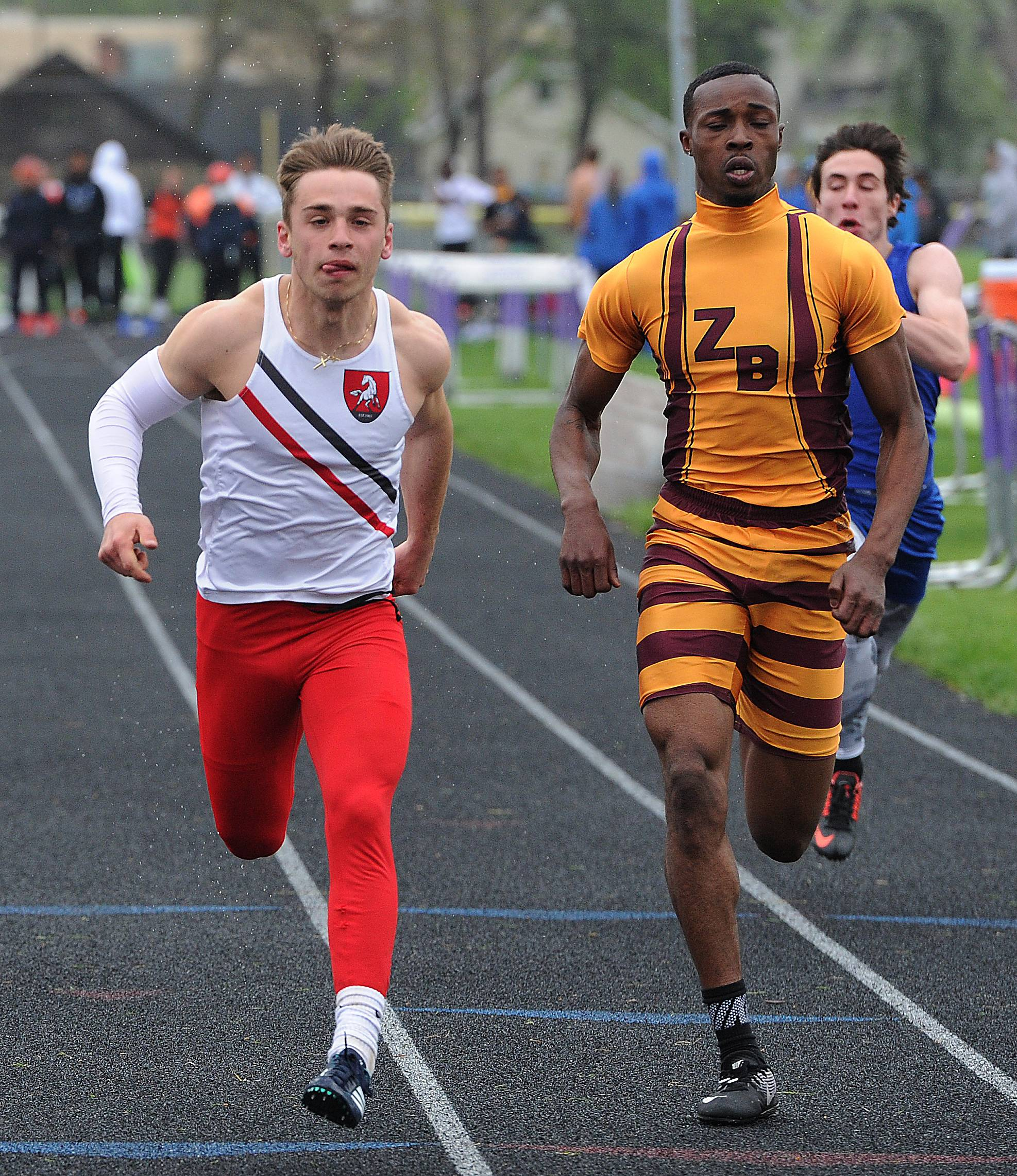 Mundelein's Bobby Nuzzo, left, wins the 100-meter dash just ahead of Zion-Benton's Cortez Sawyer in the North Suburban Conference meet Saturday in Waukegan.