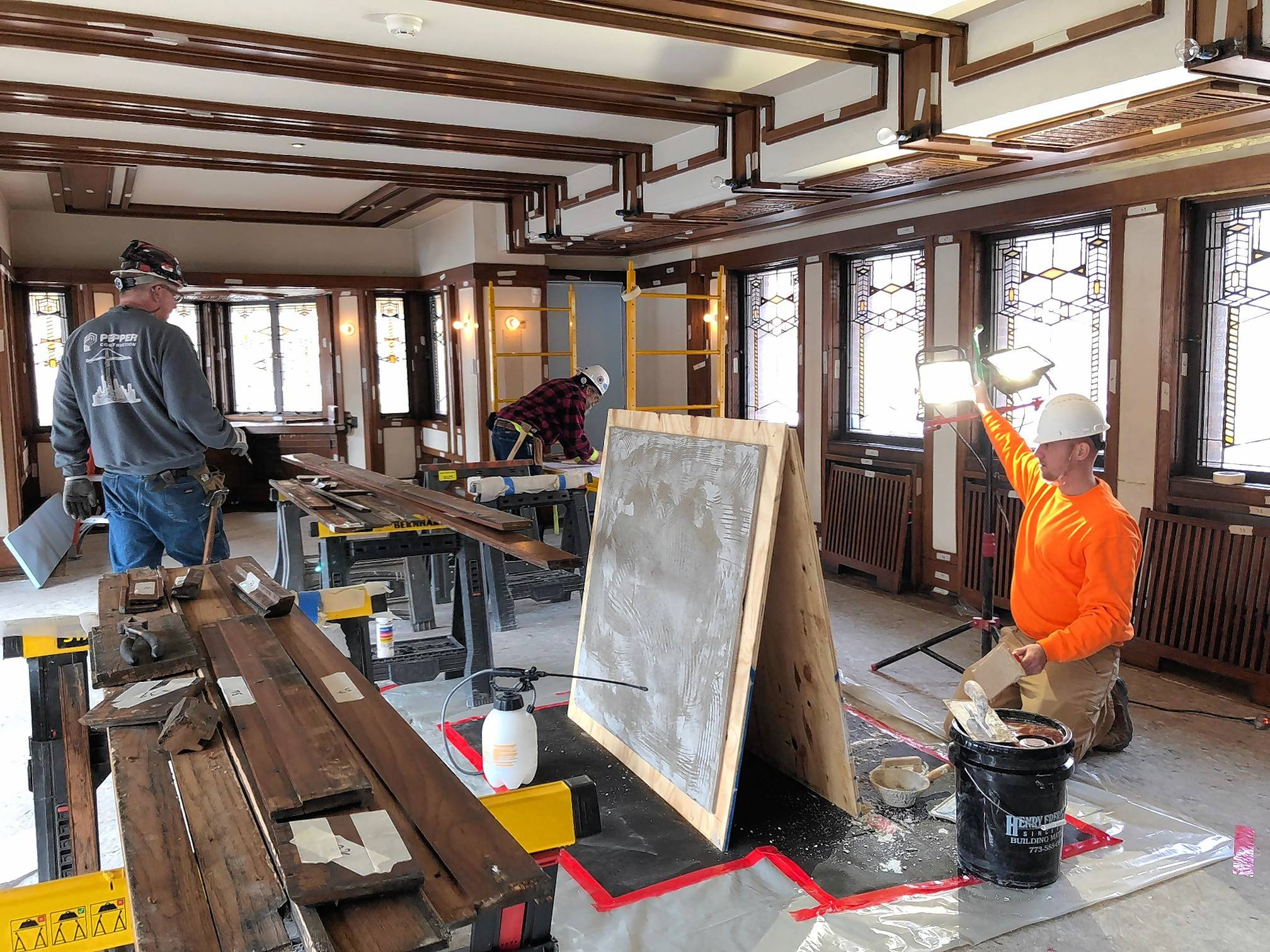 Robie House has three different lime putty plaster finishes. Here, workers prepare several of 24 sample lime putty panels that were produced and evaluated for putty mix, aggregate match, color and original finish match.