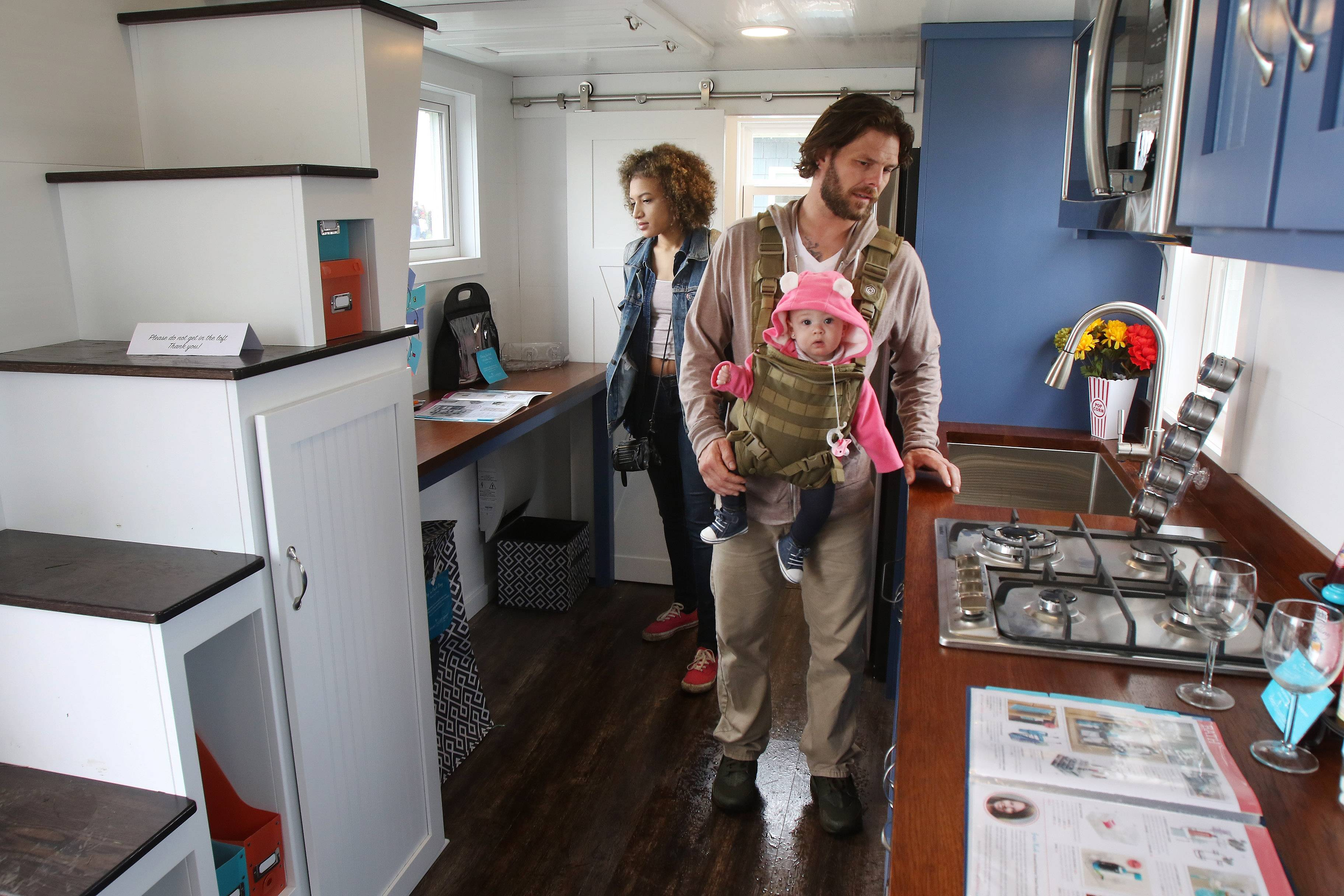 Chris Bergeron of Chicago carries his 6-month-old daughter, Rain Nova, as he looks at the inside of a model with his wife, Shy Jones, during the 2018 Chicago Tiny House Show on Sunday at Boomers Stadium in Schaumburg.