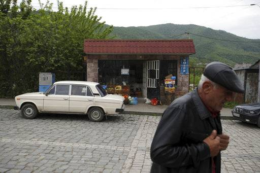 In this photo taken on Sunday, May 6, 2018, an elderly man passes outside a small market in Idjevan, northern Armenia the home town of the Armenian protest leader Nikol Pashinian. Hope has bloomed in the hometown of Armenia's newly-named prime minister, for people see him as a man who was able to articulate their anger and will now focus on their needs. Nikol Pashinian, who spearheaded weeks of anti-government protests, was named the country's new leader on May 8. Like the rest of the country, his hometown Idjevan, a city of 20,000 that sits on a key highway linking Armenia with Georgia, has been plagued by unemployment and grinding poverty after a plant processing bentonite clay and other factories closed years ago.
