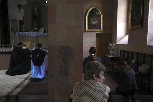 "In this photo taken on Sunday, May 6, 2018, pilgrims pray in an Armenian Orthodox church in Idjevan, northern Armenia the home town of the Armenian protest leader Nikol Pashinian. Hope has bloomed in the hometown of Armenia's newly-named prime minister, for people see him as a man who was able to articulate their anger and will now focus on their needs. Nikol Pashinian, who spearheaded weeks of anti-government protests, was named the country's new leader on May 8. Like the rest of the country, his hometown Idjevan, a city of 20,000 that sits on a key highway linking Armenia with Georgia, has been plagued by unemployment and grinding poverty after a plant processing bentonite clay and other factories closed years ago. His father recalled that his son once told him: ""If I don't fight, how will our people live? In poverty? Unemployment?�"