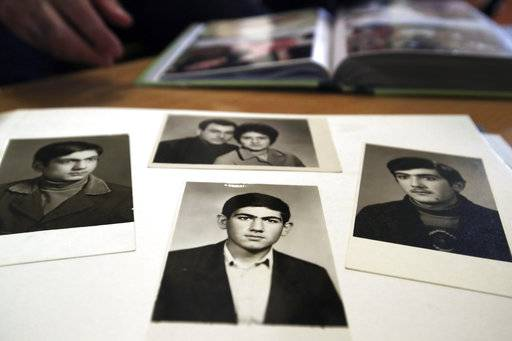 In this photo taken on Sunday, May 6, 2018, an old photo of the Armenian protest leader Nikol Pashinian, center, is seen in the family photo album in Idjevan town, northern Armenia. Hope has bloomed in the hometown of Armenia's newly-named prime minister, for people see him as a man who was able to articulate their anger and will now focus on their needs. Nikol Pashinian, who spearheaded weeks of anti-government protests, was named the country's new leader on May 8. Like the rest of the country, his hometown Idjevan, a city of 20,000 that sits on a key highway linking Armenia with Georgia, has been plagued by unemployment and grinding poverty after a plant processing bentonite clay and other factories closed years ago.