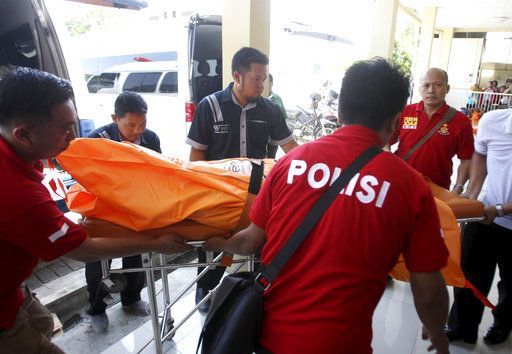 Police officers carry a body bag containing one of the victims of Sunday's explosions upon arrival at a hospital in Surabaya, East Java, Indonesia, Monday, May 14, 2018. The flurry of attacks in the country's second largest city have raised concerns that previously beaten down militant networks in the world's most populous Muslim-majority nation have been reinvigorated by the return of some of the estimated 1,100 Indonesians who went to fight with the Islamic State group in Syria.