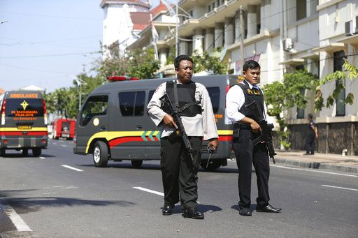 Officers stand guard following an attack at the local police headquarters in Surabaya, East Java, Indonesia, Monday, May 14, 2018. The police headquarters in Indonesia's second largest city was attacked Monday by suspected militants who detonated explosives from a motorcycle, a day after suicide bombings at three churches in the city.
