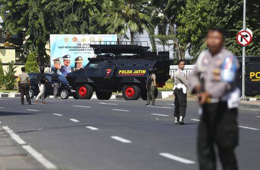 Officers block a road following an attack at the local police headquarters in Surabaya, East Java, Indonesia, Monday, May 14, 2018. The police headquarters in Indonesia's second largest city was attacked Monday by suspected militants who detonated explosives from a motorcycle, a day after suicide bombings at three churches in the city.