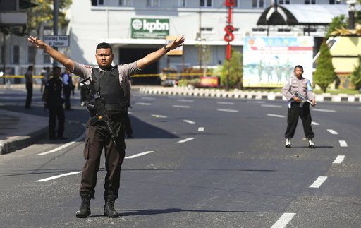 An officer gestures as police block a road outside local police headquarters following an attack in Surabaya, East Java, Indonesia, Monday, May 14, 2018. The police headquarters in Indonesia's second largest city was attacked Monday by suspected militants who detonated explosives from a motorcycle, a day after suicide bombings at three churches in the city by members of one family killed a number of people.