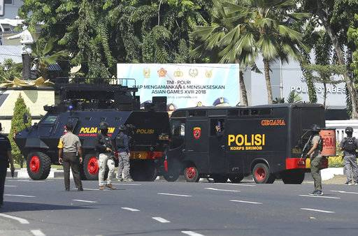 Police vehicles are parked outside local police headquarters following an attack in Surabaya, East Java, Indonesia, Monday, May 14, 2018. The police headquarters in Indonesia's second largest city was attacked Monday by suspected militants who detonated explosives from a motorcycle, a day after suicide bombings at three churches in the city by members of one family killed a number of people.