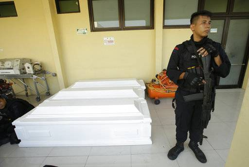 A police officer stands guard near coffins prepared for the victims of Sunday's church attacks at a hospital in Surabaya, Indonesia, Monday, May 14, 2018. Coordinated suicide bombings carried out by members of the same family struck three churches in Indonesia's second-largest city Sunday, police said, as the world's most populous Muslim nation recoiled in horror at one of its worst attacks since the 2002 Bali bombings.