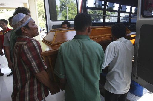 Family members put the coffin containing the body of one of the victims of Sunday's church attacks into an ambulance for a funeral, at the police hospital in Surabaya, East Java, Indonesia, Monday, May 14, 2018. The flurry of attacks in the country's second largest city have raised concerns that previously beaten down militant networks in the world's most populous Muslim-majority nation have been reinvigorated by the return of some of the estimated 1,100 Indonesians who went to fight with the Islamic State group in Syria.