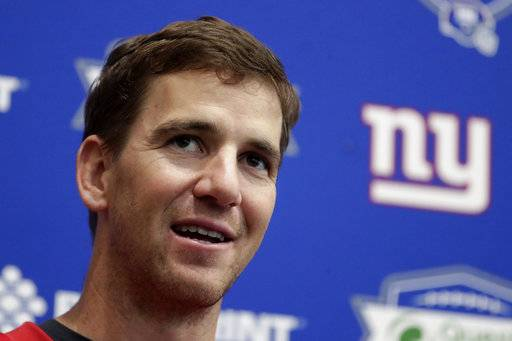 "FILE - In an April 25, 2018 file photo, New York Giants quarterback Eli Manning speaks to reporters during NFL football training camp, in East Rutherford, N.J. Jury selection is scheduled to begin on Monday, May 14, 2018, in a New Jersey memorabilia dealer's lawsuit that accuses New York Giants quarterback Eli Manning of conspiring with the team's equipment staff to sell bogus ""game-used"" helmets to unsuspecting collectors as part of a long-running scam."