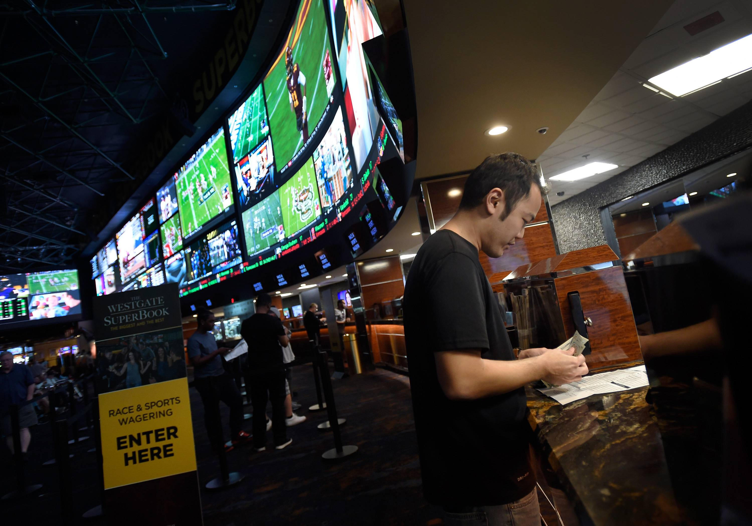 Efforts to legalize sports betting in Illinois will accelerate as a result of a U.S. Supreme Court decision announced Monday opening the door to such action, the state senator who heads the chamber's gaming committee said. Here, customer makes a sports bet at the Race & Sports SuperBook in Las Vegas last year.