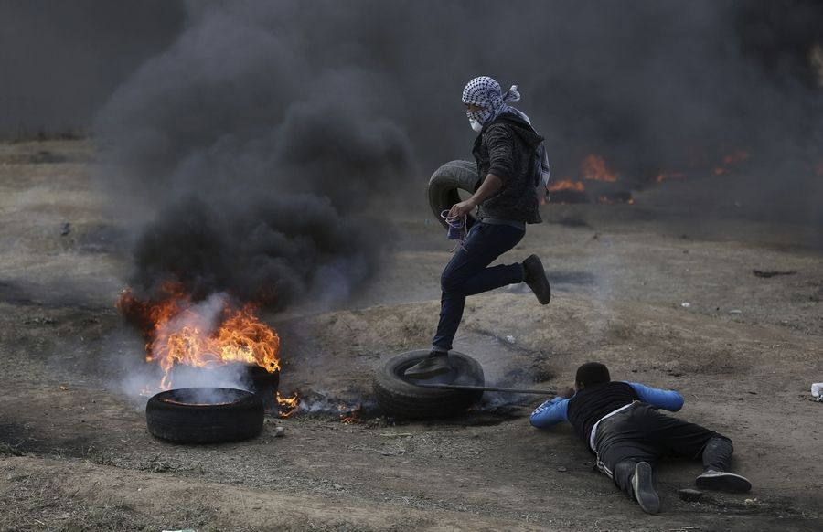 Palestinian protesters burn tires Monday during a protest on the Gaza Strip's border with Israel. Thousands of Palestinians are protesting near Gaza's border with Israel, as Israel prepared for the festive inauguration of a new U.S. Embassy in contested Jerusalem.