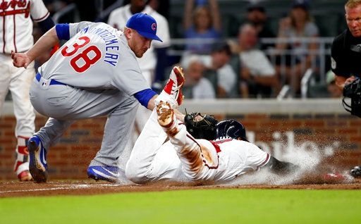 Atlanta Braves' Johan Camargo (17) is tagged out by Chicago Cubs relief pitcher Mike Montgomery (38) as he tries to score on a wild pitch in the fifth inning of a baseball game Tuesday, May 15, 2018, in Atlanta.