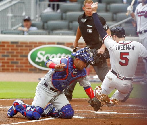 Atlanta Braves first baseman Freddie Freeman (5) is tagged out by Chicago Cubs catcher Willson Contreras (40) in the first inning of a baseball game Tuesday, May 15, 2018, in Atlanta.