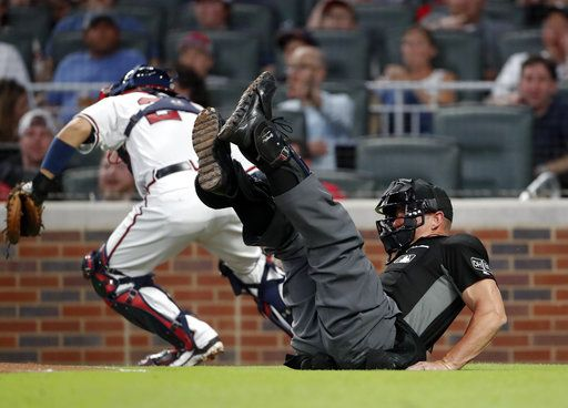 Umpire Jim Wolf (28) falls as he collides with Atlanta Braves catcher Kurt Suzuki (24), background, who was chasing a dropped third strike in the fourth a inning of a baseball game against the Chicago Cubs, Tuesday, May 15, 2018, in Atlanta. A run scored.
