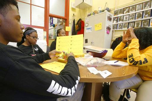 "Audrey Wright, right, quizzes fellow members of the Peace Warriors group at Chicago's North Lawndale College Prep High School on Thursday, April 19, 2018. Wright, who is a junior and the group's current president, was asking the students, from left, freshmen Otto Lewellyn III and Simone Johnson and sophomore Nia Bell, about a symbol used in the group's training on conflict resolution and team building. The students also must memorize and regularly recite the Rev. Martin Luther King's ""Six Principles of Nonviolence."""