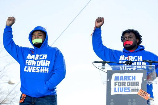 "FILE - In this Saturday, March 24, 2018 file photo, Alex King, right, and D'Angelo McDade, left, both graduating seniors at North Lawndale College Prep High School in Chicago raise their fists in the air as they arrive to speak during the ""March for Our Lives"" rally in Washington. Both are Peace Warriors at their school and both have been impacted by gun violence. King lost a 16-year-nephew last year and McDade was shot in the leg."