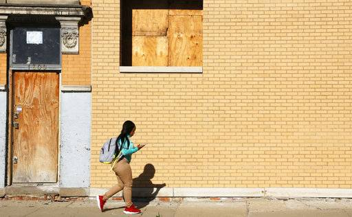"Alexis Willis, a high school freshman, listens to music on her phone as she walks to school in Chicago's North Lawndale neighborhood on Friday, April 27, 2018. She said school shootings sadden her greatly, though she and her peers worry even more about gun violence outside of school. Her 16-year-old cousin was shot and killed in early April, causing concerns about her own safety. ""I don't want to die this summer,"" she said."