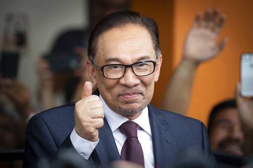 Malaysia's jailed opposition icon Anwar Ibrahim reacts to supporters as he leaves a hospital in Kuala Lumpur, Malaysia, Wednesday, May 16, 2018. Prime Minister Mahathir Mohamad said Malaysia's king had agreed to pardon Anwar, who was jailed in 2015 for sodomy in a conviction that he said was politically motivated.