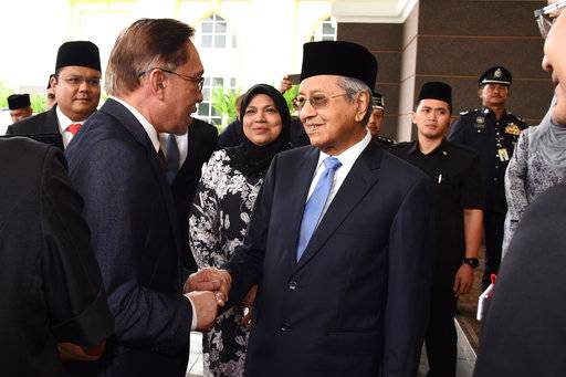 In this photo taken and released on Wednesday, May 16, 2018, by the Malaysia Information Ministry, shows reformist icon Anwar Ibrahim, left, shakes hands with new Malaysia's Prime Minister Mahathir Mohamad, center, as he arrives to the National Palace to meet with Malaysia's King Muhammad V following his release from custody in Kuala Lumpur, Malaysia on Wednesday, May 16, 2018. (Malaysia Information Ministry via AP)