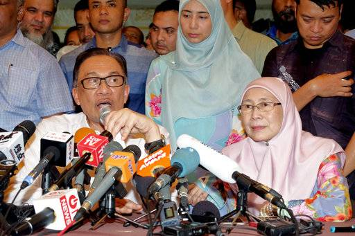 Malaysia's reformist icon Anwar Ibrahim speaks next to his wife Wan Azizah, President of Justice Party, during a press conference at their house in Kuala Lumpur, Malaysia, Wednesday, May 16, 2018. Malaysia's reformist icon Anwar Ibrahim has been freed from custody after receiving a royal pardon, paving the way for a political comeback following his alliance's stunning election victory.