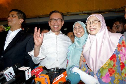 Malaysia's reformist icon Anwar Ibrahim, center, smiles next to his daughter, second right, and his wife Wan Azizah, President of Justice Party, right, at their house in Kuala Lumpur, Malaysia, Wednesday, May 16, 2018. Malaysia's reformist icon Anwar Ibrahim has been freed from custody after receiving a royal pardon, paving the way for a political comeback following his alliance's stunning election victory.