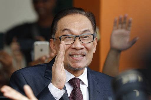Malaysia jailed opposition icon Anwar Ibrahim waves to supporters as he leaves a hospital in Kuala Lumpur, Malaysia, Wednesday, May 16, 2018. Prime Minister Mahathir Mohamad said Malaysia's king had agreed to pardon Anwar, who was jailed in 2015 for sodomy in a conviction that he said was politically motivated.
