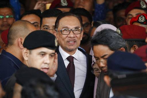 Malaysia jailed opposition icon Anwar Ibrahim waves to supporters as he leave a hospital in Kuala Lumpur, Malaysia, Wednesday, May 16, 2018. Prime Minister Mahathir Mohamad said Malaysia's king had agreed to pardon Anwar, who was jailed in 2015 for sodomy in a conviction that he said was politically motivated.