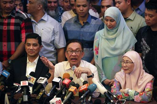 Malaysia's reformist icon Anwar Ibrahim, center, speaks next to his wife Wan Azizah, President of Justice Party, right, during a press conference at their residence in Kuala Lumpur, Malaysia, May 16, 2018. Anwar has been freed from custody after receiving a pardon from the king, paving the way for a political comeback following his alliance's stunning election victory.