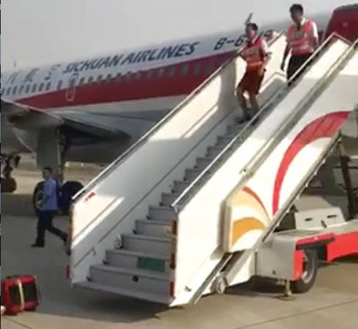In this photo taken Monday, May 16, 2018, and released by a passenger who wishes to remain anonymous, ground crew are seen leaving the Sichuan Airline flight that made an emergency landing in Chengdu in southwestern China's Sichuan province. Chinese authorities and Airbus are investigating why the plane's cockpit windshield detached during a flight, forcing an emergency landing in an unusual mishap in one of the world's fastest growing aviation markets. (Passenger via AP)