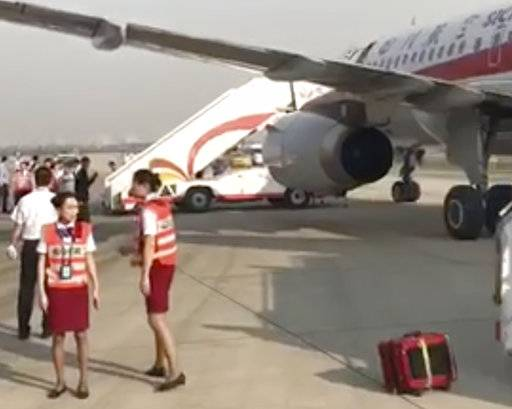 In this photo taken Monday, May 16, 2018, and released by a passenger who wishes to remain anonymous, ground crew are seen near the Sichuan Airline flight that made an emergency landing in Chengdu in southwestern China's Sichuan province. Chinese authorities and Airbus are investigating why the plane's cockpit windshield detached during a flight, forcing an emergency landing, in an unusual mishap in one of the world's fastest growing aviation markets. (Passenger via AP)