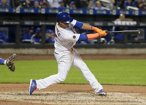 New York Mets' Juan Lagares swings for a two-run single against the Toronto Blue Jays during the fourth inning of a baseball game Tuesday, May 15, 2018, in New York.