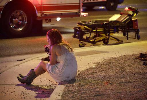 FILE - In this Oct. 2, 2017 file photo a woman sits on a curb at the scene of a shooting outside a music festival on the Las Vegas Strip. Police in Las Vegas plan to release witness statements and officer reports of the Oct. 1 gunfire that killed 58 people and injured hundreds in the deadliest mass shooting in modern U.S. history. The scheduled release of documents on Wednesday, May 16, 2018, comes more than seven months after the shooting on the Las Vegas Strip.