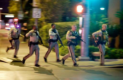 FILE - In this Oct. 1, 2017, file photo, police run toward the scene of a shooting near the Mandalay Bay resort and casino on the Las Vegas Strip in Las Vegas. Police in Las Vegas plan to release witness statements and officer reports of the Oct. 1 gunfire that killed 58 people and injured hundreds in the deadliest mass shooting in modern U.S. history. The scheduled release of documents on Wednesday, May 16, 2018, comes more than seven months after the shooting on the Las Vegas Strip.