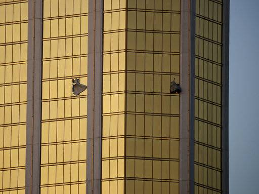 FILE - In this Monday, Oct. 2, 2017 file photo, drapes billow out of broken windows at the Mandalay Bay resort and casino on the Las Vegas Strip, following a mass shooting at a music festival in Las Vegas. Police in Las Vegas plan to release witness statements and officer reports of the Oct. 1 gunfire that killed 58 people and injured hundreds in the deadliest mass shooting in modern U.S. history. The scheduled release of documents on Wednesday, May 16, 2018, comes more than seven months after the shooting on the Las Vegas Strip.