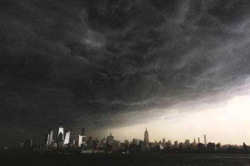 In this Tuesday, May 15, 2018 photo, storm clouds gather over New York city seen from the Hudson River. A line of strong storms pushed across New York City and badly disrupted the evening commute, stranding thousands of train riders.