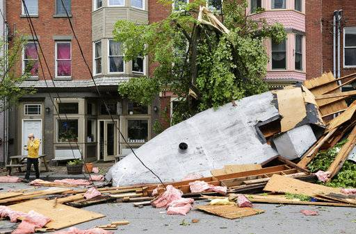 A man walks past damage caused by a storm in Newburgh, N.Y., Wednesday, May 16, 2018. Powerful storms pounded the Northeast on Tuesday with torrential rain and marble-sized hail, leaving thousands of homes and businesses without power.