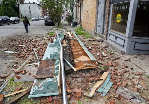 Debris from a storm-damaged building lies in the street in Newburgh, N.Y., Wednesday, May 16, 2018. Powerful storms pounded the Northeast on Tuesday with torrential rain and marble-sized hail, leaving  thousands of homes and businesses without power.