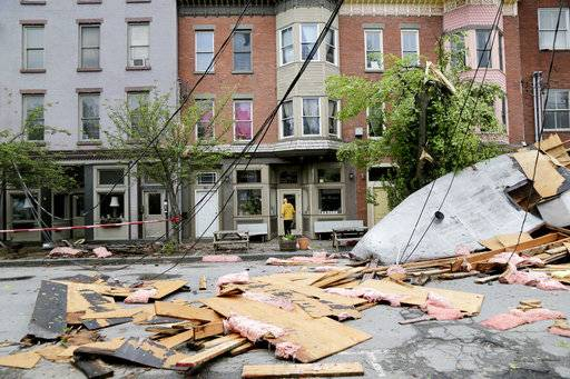 A man enters a building past debris caused by a storm in Newburgh, N.Y., Wednesday, May 16, 2018. Powerful storms pounded the Northeast on Tuesday with torrential rain and marble-sized hail, leaving thousands of homes and businesses without power.