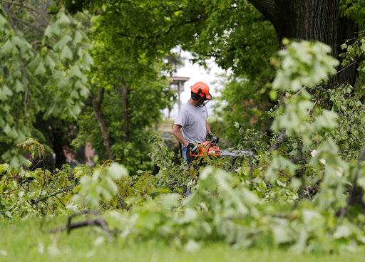 A man clears downed branches and debris on the grounds of Washington's Headquarters State Historic Site in Newburgh, N.Y., Wednesday, May 16, 2018. Powerful storms pounded the Northeast on Tuesday with torrential rain and marble-sized hail, leaving thousands of homes and businesses without power.