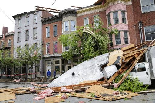 Men stand near buildings damaged by a storm in Newburgh, N.Y., Wednesday, May 16, 2018. Powerful storms pounded the Northeast on Tuesday with torrential rain and marble-sized hail, leaving thousands of homes and businesses without power.