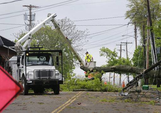 A utility crew works to clear a roadway of storm debris in Newburgh, N.Y., Wednesday, May 16, 2018. Powerful storms pounded the Northeast on Tuesday with torrential rain and marble-sized hail, leaving thousands of homes and businesses without power.
