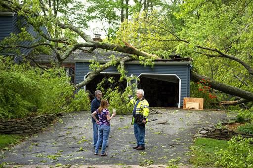 Chris Fletcher,left, and his wife Noel survey the storm damage to their home in Cheshire with a Cheshire volunteer firefighter on Wednesday, May 16, 2018. Residents in the Northeast cleaned up Wednesday, a day after powerful storms pounded the region with torrential rain and marble-sized hail, leaving more then 200,000 homes and businesses without power. (Patrick Raycraft/Hartford Courant via AP)