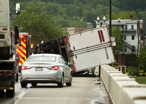 A Freightliner tractor-trailer, which was overturned by strong winds associated with a thunderstorm, rests on a barrier on a bridge crossing the Susquehanna River at Danville, Pa., on Tuesday, May 15, 2018. The driver, Mariusz Jarosz, of Des Plaines, Illinois, suffered a hand injury and was transported to a hospital. (Larry Deklinski/The News-Item via AP)