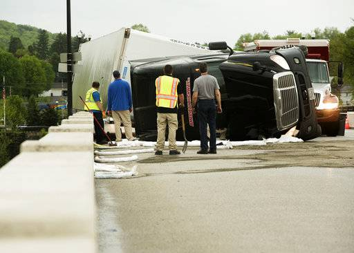 Emergency personnel look at a Freightliner tractor-trailer, which was overturned by strong winds associated with a thunderstorm, while crossing the Susquehanna River at Danville, Pa., on Tuesday, May 15, 2018. The driver, Mariusz Jarosz, of Des Plaines, Illinois, suffered a hand injury and was transported to a hospital. (Larry Deklinski/The News-Item via AP)