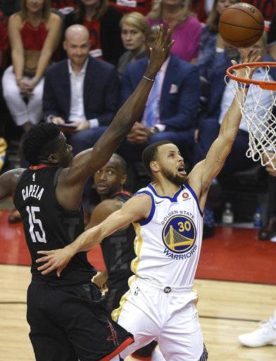 Golden State Warriors guard Stephen Curry (30) drives to the basket as Houston Rockets center Clint Capela (15) defends during the first half of Game 2 of the NBA basketball playoffs Western Conference finals Wednesday, May 16, 2018, in Houston.