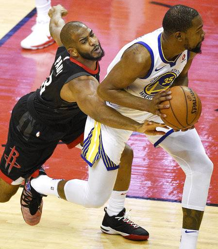 Houston Rockets guard Chris Paul, left, reaches for the ball held by Golden State Warriors forward Kevin Durant during the first half of Game 2 of the NBA basketball playoffs Western Conference finals Wednesday, May 16, 2018, in Houston.