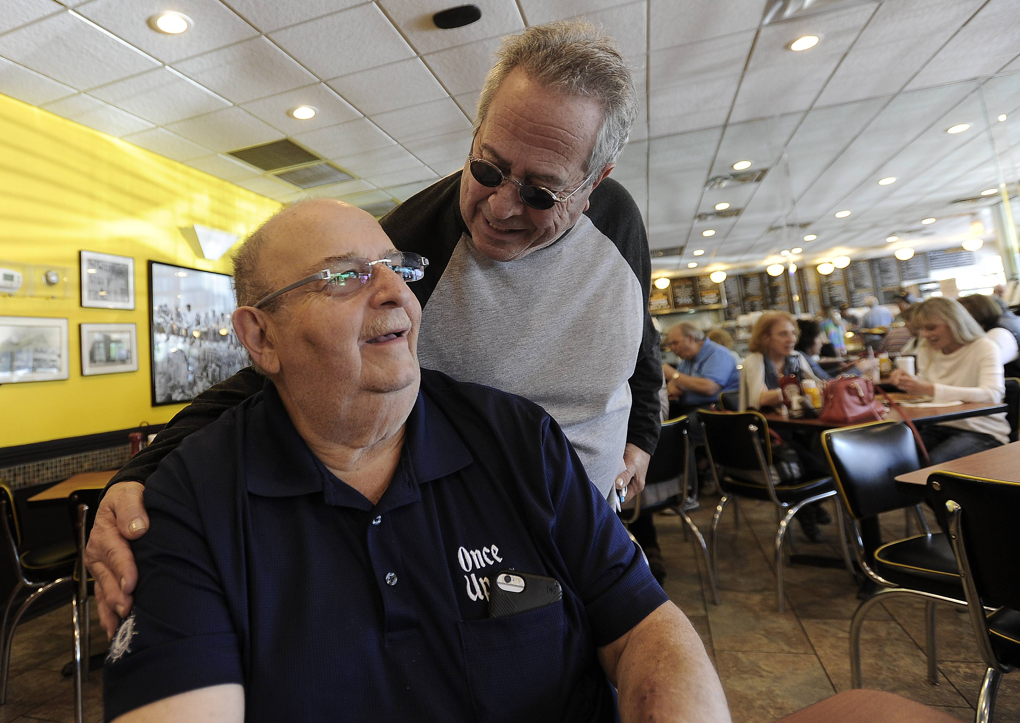 "Gerry Geffen of Lincolnshire, owner of Once Upon A Grill in Northbrook, sits in his restaurant as his friend Bruce Siegel of Highland Park stops by to say hello. Siegel was surprised to hear his friend needs a donated kidney, news employees are trying to get out by wearing T-shirts declaring ""The Bagel Man Needs a Kidney."""